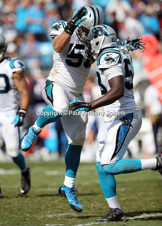 Carolina Panthers outside linebacker A.J. Klein (56) jumps and celebrates with Carolina Panthers outside linebacker Thomas Davis (58) after he intercepts a fourth quarter pass in Houston Texans territory during the 2015 NFL week 2 regular season football game against the Houston Texans on Sunday, Sept. 20, 2015 in Charlotte, N.C. The Panthers won the game 24-17. (©Paul Anthony Spinelli)