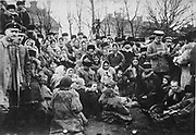 Crowd, possibly  of Jewish refugees in the open air in Russia. One of the three uniformed officials with them is examining their papers. Photograph c1912.