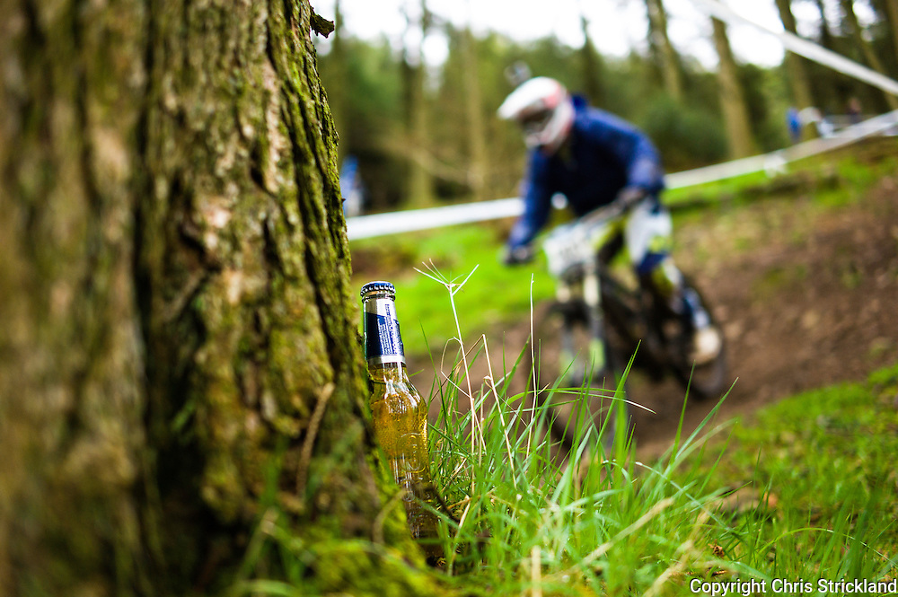 Ae Forest, Dumfries, Scotland, UK. 25th April 2015. Downhill Mountain Bikers pass a beer bottle cooling by a tree on the 7Stanes course at Ae during the Scottish Downhill Association racing.