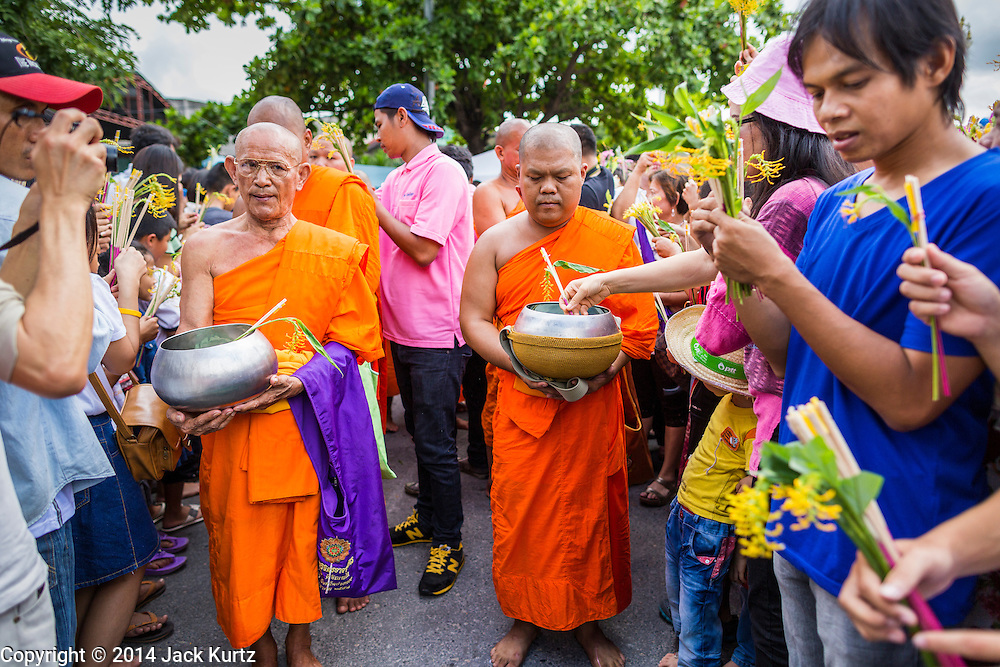 """12 JULY 2014 - PHRA PHUTTHABAT, SARABURI, THAILAND: People present monks with flowers during the Tak Bat Dok Mai at Wat Phra Phutthabat in Saraburi province of Thailand. Wat Phra Phutthabat is famous for the way it marks the beginning of Vassa, the three-month annual retreat observed by Theravada monks and nuns. The temple is highly revered in Thailand because it houses a footstep of the Buddha. On the first day of Vassa (or Buddhist Lent) people come to the temple to """"make merit"""" and present the monks there with dancing lady ginger flowers, which only bloom in the weeks leading up Vassa. They also present monks with candles and wash their feet. During Vassa, monks and nuns remain inside monasteries and temple grounds, devoting their time to intensive meditation and study. Laypeople support the monks by bringing food, candles and other offerings to temples. Laypeople also often observe Vassa by giving up something, such as smoking or eating meat. For this reason, westerners sometimes call Vassa """"Buddhist Lent.""""    PHOTO BY JACK KURTZ"""