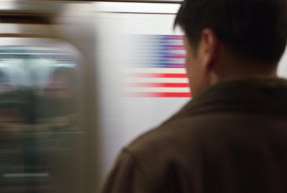 Man watching speeding subway train with image of American flag