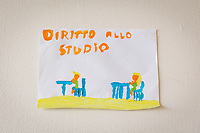 """NAPLES, ITALY - 16 MARCH 2018: A child's painting quoting """"The right to study"""" is seen here at the headquarters of  """"Il Tappeto di Iqbal"""" (Iqbal's carpet), a non-profit cooperative in Barra, the estern district of Naples, Italy, on March 16th 2018.<br /> <br /> Il Tappeto di Iqbal (Iqbal's Carpet) is a non-profit cooperative founded in 2015 and Save The Children partner since 2015 that operates in the Naple's eastern neighborhood of Barra children in the arts of circus, theater and parkour. It was named after Iqbal Masih, a Pakistani boy who escaped from life as a child slave and became an activist against bonded labor in the 1990s.<br /> Barra, which is home to some 45,000 people, has the highest rate of school dropouts in the Italian region of Campania. Once a thriving industrial community, many of the factories were destroyed in a 1980 earthquake and never rebuilt. The resulting de-industrialization turned Barra into a poor, decaying neighborhood. There are no cinemas, theaters, parks or public spaces in Barra.<br /> The vast majority of children from poor families are faced with the choice of working in the black economy or joining the ranks of the organised crime.<br /> Recently, Save the Children Italy opened a number of educational and social spaces in Barra. The centers, known as Punti Luce, or points of light, aim to help local kids stay out of the ranks of the organised crime and have also become hubs for Iqbal's Carpet to work."""