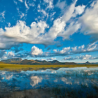 clouds reflecting in a pond along the rocky mountain front