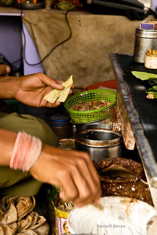 A close up of a Paanwala making Paan at a roadside stall in Varanasi, Uttar Pradesh, India