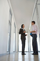 Two Businesspeople Talking in Corridor low angle view.