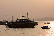 Halong Bay. Tourist and rowing boats at sunset.