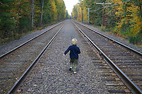 A 4-year-old boy runs between railroad tracks with fall colors, near Walden Pond, Concord, MA. MR.