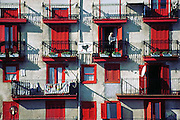 A man stands on the balcony of a red shuttered apartment building in Mundacca, Basque region, Spain