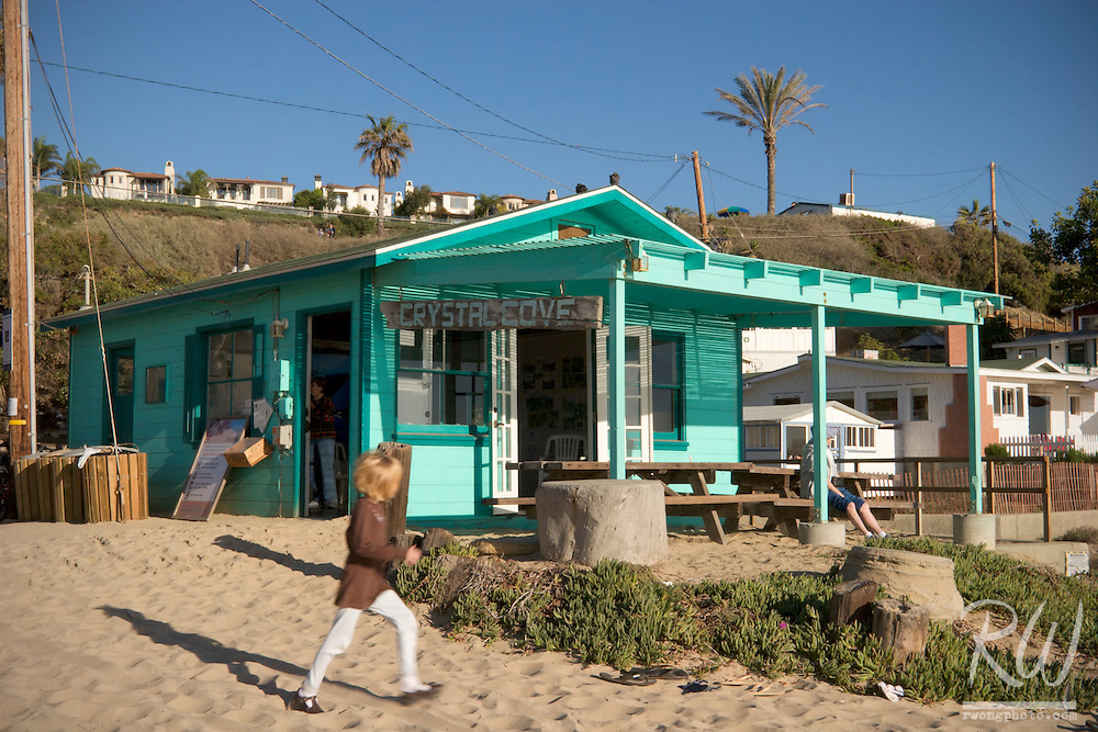 Girl Walking Past Beachcomber Cafe at Crystal Cove Cottages Historic District, California