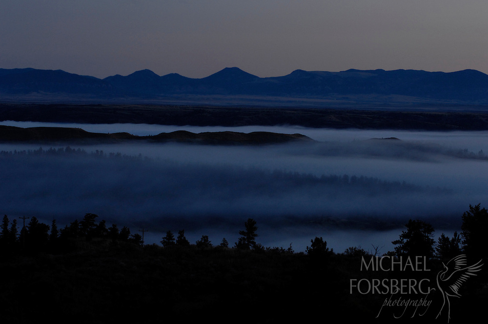 Thick fog hangs over river valley and breaks before dawn as Little Rockies loom in the distance.  Charles M Russell National Wildlife Refuge, Missouri River Breaks, Montana.