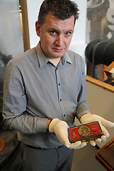 © Licensed to London News Pictures. 19/12/2013. Tin of chocolate sent to troops overseas in 1900 for new New Year by Queen Victoria is on show for the first time at Firepower Museum, pictured with Richard Smith-Gore from the museum. Christmas boxes for solders from the present day back to 1900 have gone on show at the Firepower Musuem in South East London. The collection includes a New Years christmas tin sent in 1900 by Queen Victoria. Some historians think she should be credited with the annual gift box rather than Princess Mary who was responsible for the Christmas box, sent in 1914. It's the first time the Victorian box has gone on show at the museum, which is one of the oldest military museums in the world. Please contact Richard Smith-Gore at Firepower for quotes and additional info. Credit : Rob Powell/LNP