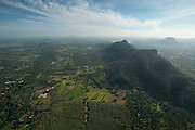 Aerial view of plains and mountain covered in forest.