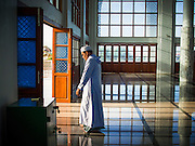 28 JULY 2014 - KHLONG HAE, SONGKHLA, THAILAND: A man walks out of Songkhla Central Mosque before Eid services. Eid al-Fitr is also called Feast of Breaking the Fast, the Sugar Feast, Bayram (Bajram), the Sweet Festival and the Lesser Eid, is an important Muslim holiday that marks the end of Ramadan, the Islamic holy month of fasting.   PHOTO BY JACK KURTZ
