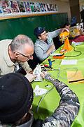 Volontärer hjälper besökarna på Repair Café i Portland att laga ett strykjärn och en köksmaskin.