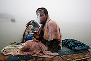 Santos Dafos smokesin the early morning on the roof of the otter's bamboo cage where he slept the night  <br /> <br /> Dharia (otter) fishermen or sea-gypsies and their animals which they use in their fishing practices; Sundarbans National Park (worlds largest littoral mangrove belt, granted UNESCO World Heritage status, December 1997 ); Khulna Division photographer in delhi photographer in delhi photographer in delhi