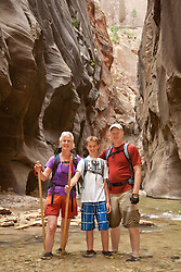 North America, United States, Utah, Zion National Park, family in slot canyon hiking the Virgin River Narrows.   MR