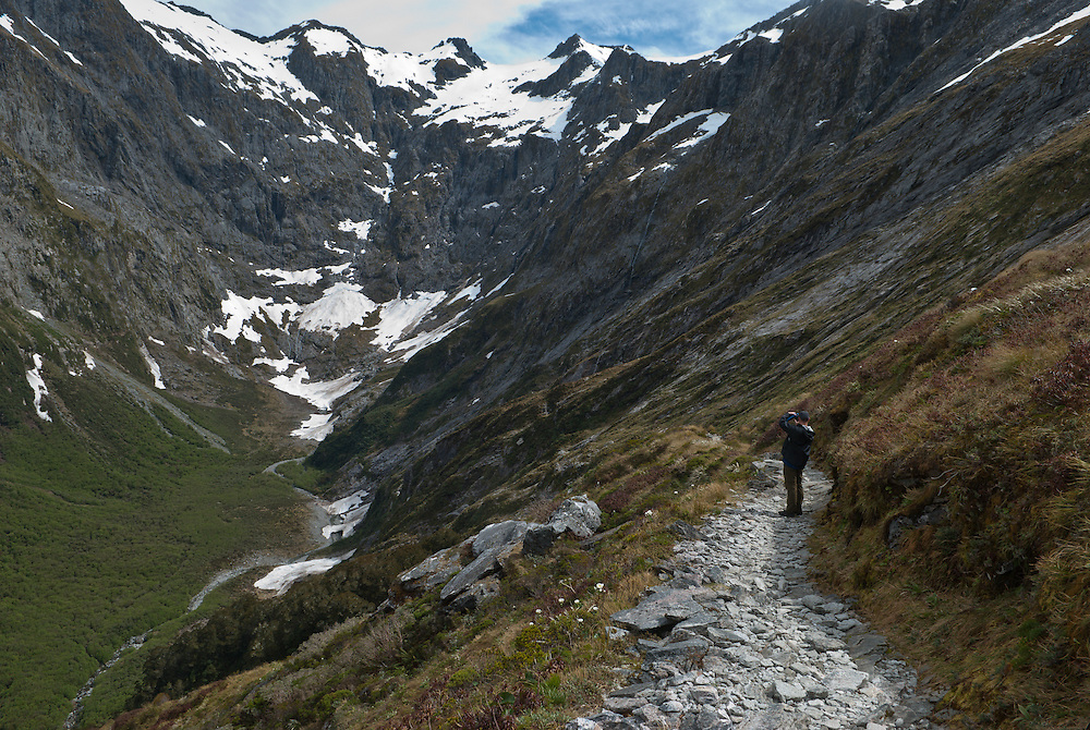 A walker photographs the steep slopes and glacial peaks of Mt Hart as seen from the ascent of Mackinnon Pass, Milford Track, New Zealand