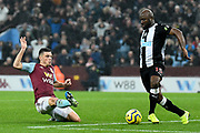 Aston Villa defender Frederic Guilbert (24) slides in to tackle Newcastle United defender (on loan from Eintracht Frankfurt) Jetro Willems (15) during the Premier League match between Aston Villa and Newcastle United at Villa Park, Birmingham, England on 25 November 2019.