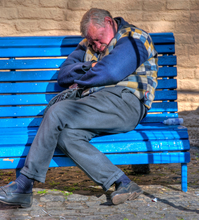 Man talking a nap on Caminito Street bench, in La Boca, Buenos Aires, Caminito is a typical tourist destination in Argentina.
