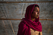 Momtaz Begum, a Rohingya woman and survivor of the massacre at Tula Toli (Min Gyi village) in Myanmar, inside her make-shift shelter at the Balukhali refugee camp in Cox's Bazar, Bangladesh. Her burns are the result of an attack by the Myanmar military who brutally raped her, then locked her in her house and set fire to the roof. Escaping the burning building she found her husband and three sons killed and her daughter badly beaten and bleeding from machete wounds to her head. Photograph by David Dare Parker