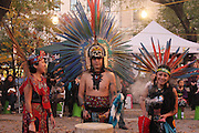 New York, New York. November 1, 2013. Yadira Aleman, Gustavo Arias, and Veronica Gomez stand in front of the crowd. Their dance group, Kalpulli Atl-Tlachinolli performed at a Dia De Los Muertos celebration outside St. Mark's Church in the Bowery. 11012013. Photo by Maya Rajamani/NYCity Photo Wire