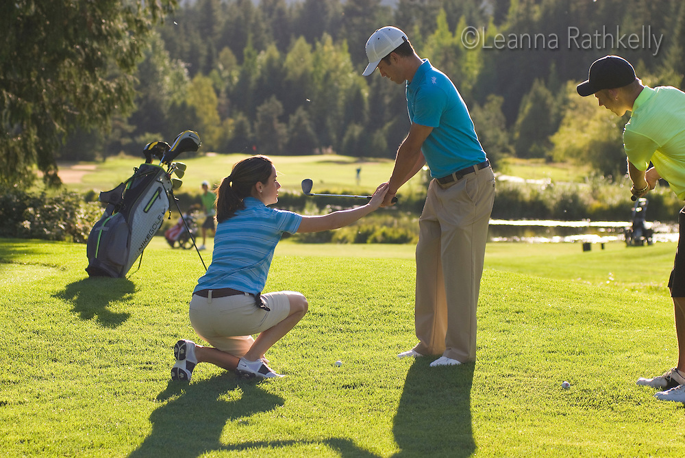 A female golf instructor teaches an on-course lesson on the Whistler Golf Course in Whistler, BC Canada.