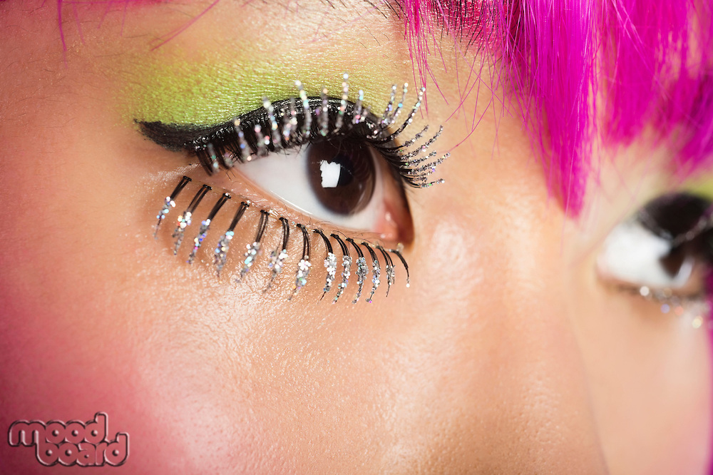 Extreme close-up of young funky woman's face with false eyelashes