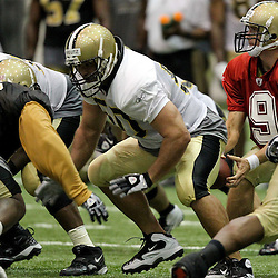 August 5, 2011; Metairie, LA, USA; New Orleans Saints center Olin Kreutz (50) snaps the ball to quarterback Drew Brees (9) during training camp practice at the New Orleans Saints practice facility. Mandatory Credit: Derick E. Hingle