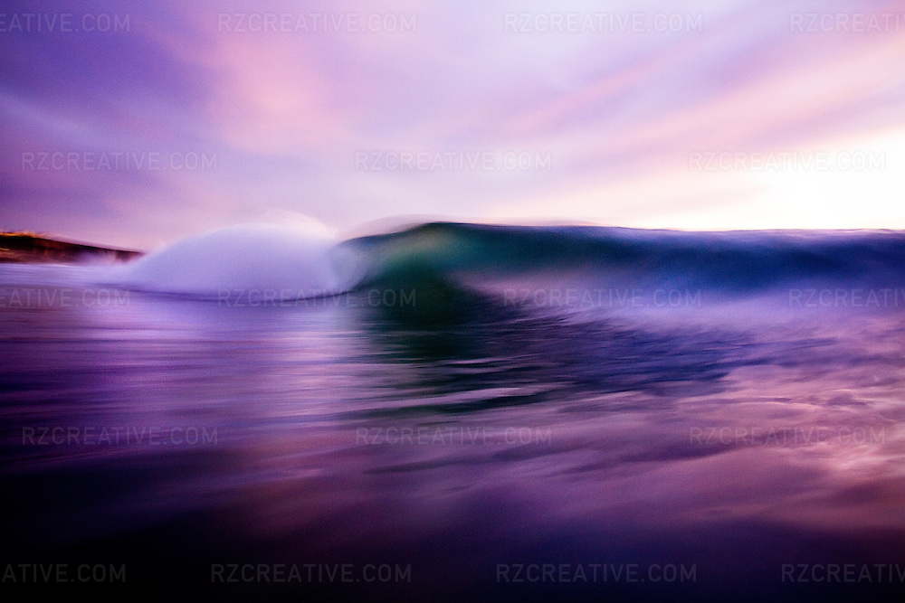 Water shot of a breaking wave with motion blur at sunset.