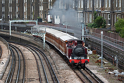 © Licensed to London News Pictures. 22/06/2019. London, UK. A Metropolitan Locomotive No 1 steam engine pulls a set of vintage coaches approaches Barons Court Undergound station to celebrate the 150th anniversary of the district line. London Transport Museum is running steam services, with vintage coaches, between Ealing Broadway and High Street Kensington over this weekend. Photo credit: Peter Macdiarmid/LNP
