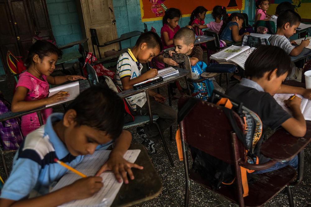 SAN PEDRO SULA, HONDURAS - MAY 23, 2014:  Children study at an elementary school in the La Pradera neighborhood, a Mara stronghold.  The police report that seven children have been murdered by Mara gang members in this neighborhood in the past month, one as young as 7-years old.  PHOTO: Meridith Kohut for The New York Times