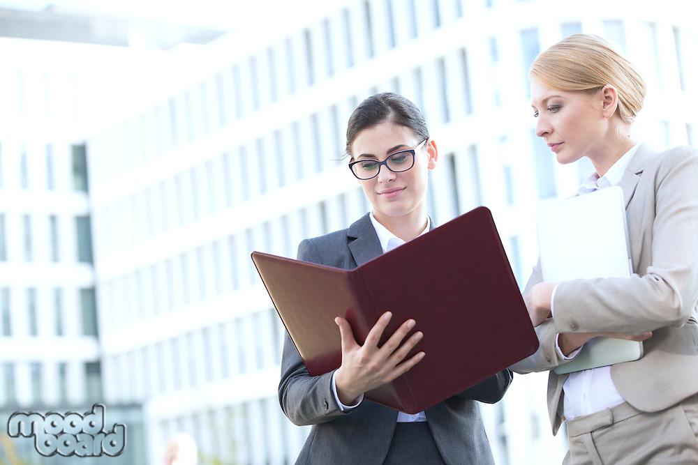 Businesswomen reading folder while standing outside office building