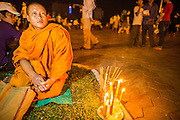 02 FEBRUARY 2013 - PHNOM PENH, CAMBODIA:  A Buddhist monk prays for former King Norodom Sihanouk with candles in Phnom Penh. Much of Phnom Penh has been shut down to honor former King Norodom Sihanouk, who ruled Cambodia from independence in 1953 until he was overthrown by a military coup in 1970. Only bars, restaurants and hotels that cater to foreign tourists are supposed to be open. The only music being played publicly is classical Khmer music. Sihanouk died in Beijing, China, in October 2012 and will be cremated during a state funeral royal ceremony on Monday, Feb. 4.    PHOTO BY JACK KURTZ