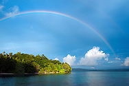 Raja Ampat Archipelago, West Papua, Indonesia, December 2010. A rainbow brings good luck after the daily thunderstorm. Thousands of small islands fringed by coral reefs and blue water mangroves litter the Raja Ampat archipelago. The turquoise and blue waters are teeming with marine life that forms the livelihood for the local Papuan population. The Raja Ampat Research & Conservation Centre (RARCC) supports the locals to develop a community based, sustainable tourism project, inviting visitors to explore their islands by sea kayak and experience the culture by staying amongst the local people in traditional style homestays. Photo by Frits Meyst / MeystPhoto.com