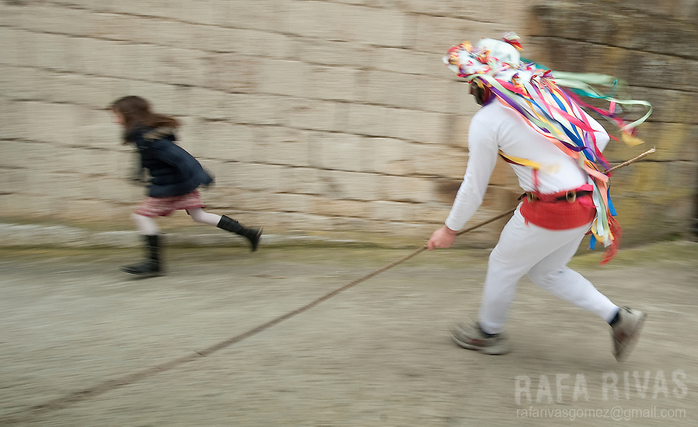 A momotxorro chases a girl during the ancient carnival of Unanu, North of Navarra province in Spain, on March 8, 2011. Momotxorros chase locals and slash them with sticks.   PHOTO/ RAFA RIVAS