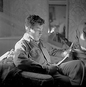 Ray Fisher sitting ina chair and reading in a house in Austria, May 1945