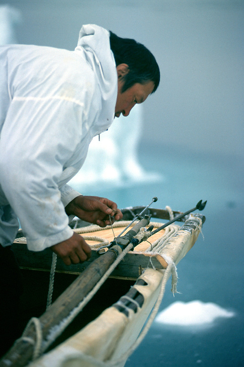 Barrow, Alaska, Alaska Native whaler prepares his umiak with harpoon and buoy for the annual bowhead whale hunt in the Chukchi Sea