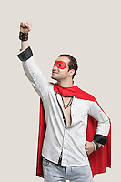 Young man in superhero costume with hand raised against gray background