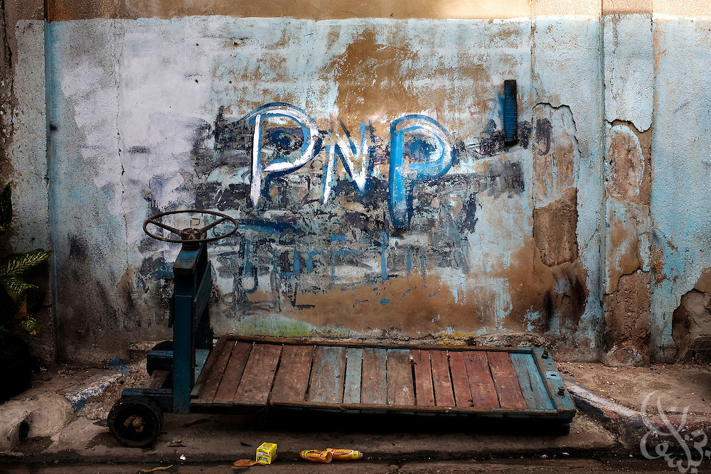 "A graffiti People's National Party (PNP) sign decorates a wall above a hand cart in the Matthews lane neighborhood of Kingston, Jamaica. Kingston is made up of a patchwork of politically allied neighborhoods, known as ""garrisons"" in which simple signs such as this serve as warnings to outsiders of the neighborhoods political allegiance."