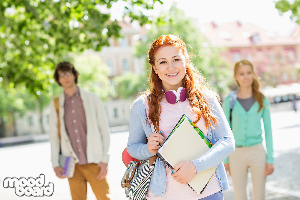 Portrait of young female student with friends in background on street