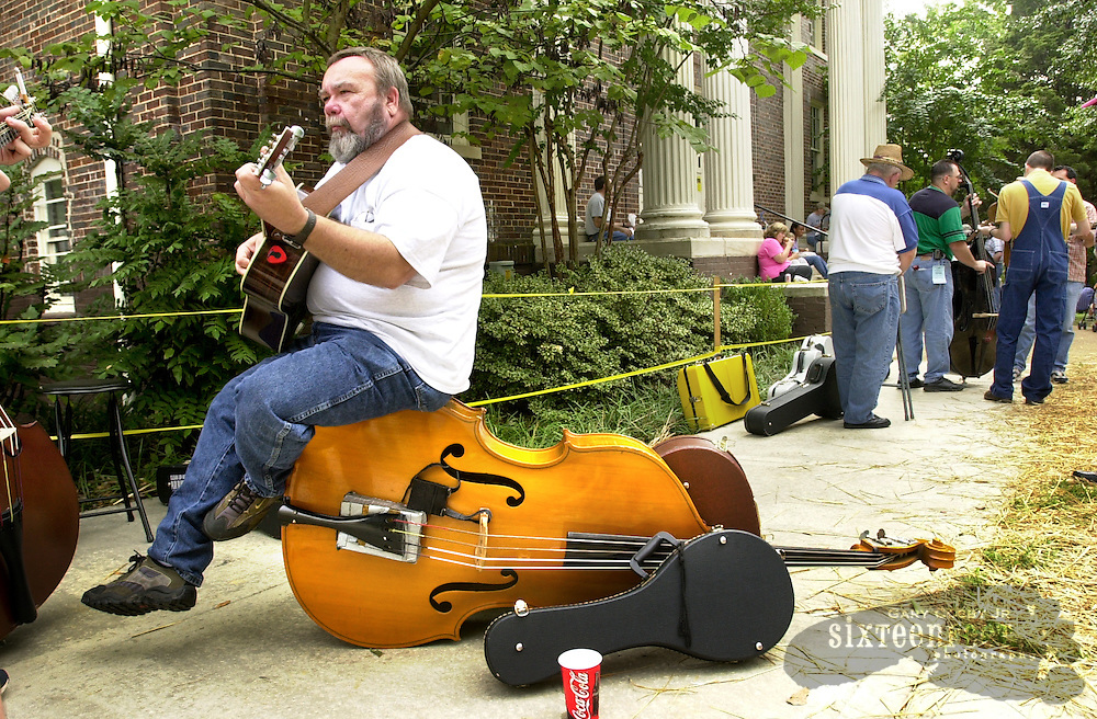 Photo by Gary Cosby Jr.  A man sits on an upright bass while playing guitar during a jam session at the Old Time Fiddler's Convention at Athens State University in Athens, Alabama.