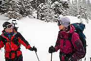 A couple of skiers plan their strategy while touring to Peter Estin hut in a snow storm in Colorado.  Telemark or AT skis with climbing skins are used to climb up steep snow slopes when doing backcountry skiing.