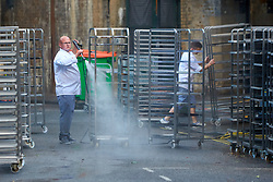 © Licensed to London News Pictures. 11/06/2017. LONDON, UK.  Bakers clean racks outside Bread Ahead in Borough Market. The market remain has remained closed since a terror attack a week ago killed eight people but is expected to begin reopening tomorrow (Monday).  Photo credit: Cliff Hide/LNP