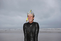Man in wetsuit wearing snorkle standing on beach portrait