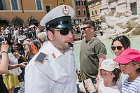 """ROME, ITALY - 20 JUNE 2017: A Roman policeman, entrusted to protect the Fountain of Trevi, blows his whistle at tourists that were sitting on the edge of the fountain in Rome, Italy, on June 20th 2017.<br /> <br /> The warm weather has brought a menacing whiff of tourists behaving badly in Rome. On April 12, a man went skinny-dipping in the Trevi fountain resulting in a viral web video and a 500 euro fine.<br /> <br /> Virginia Raggi, the mayor of Rome and a national figurehead of the anti-establishment Five Star Movement,  issued an ordinance involving harsher fines for eating, drinking or sitting on the fountains, for washing animals or clothes in the fountain water or for throwing anything other than coins into the water of the Trevi Fountain, Bernini's Four Fountains and 35 other city fountains of artistic or historic significance around the city.  """"It is unacceptable that someone use them to go swimming or clean themselves, it's an historic patrimony that we must safeguard,"""" Ms. Raggi said."""