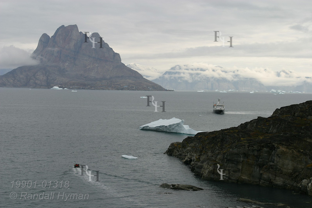 Expedition cruise ship Clipper Adventurer anchors outside cove at Qilakitsoq on the Nuussuaq Peninsula with Uummannaq Island looming behind in distance; Greenland