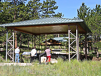 Visitors study the covered petrified sequoia stumps at Florissant Fossil Beds National Monument, Colorado.