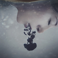 conceptual artwork of a girl's face underwater with black ink pouring out of her mouth