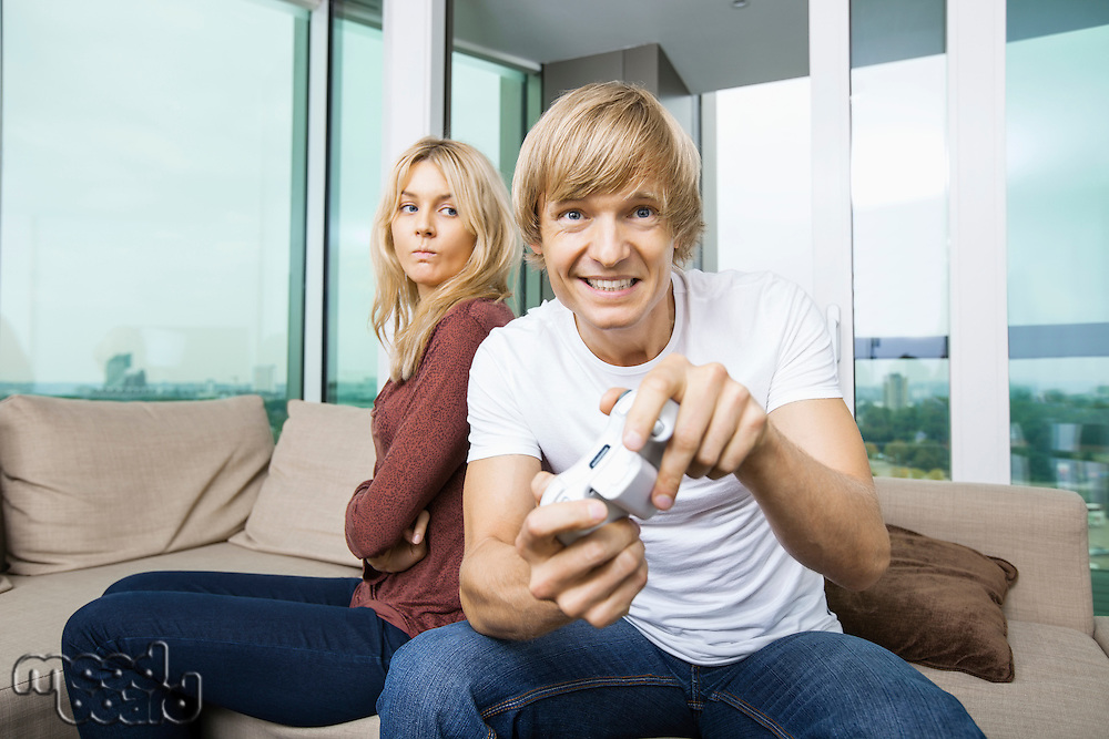 Angry woman looking at man play video game in living room at home