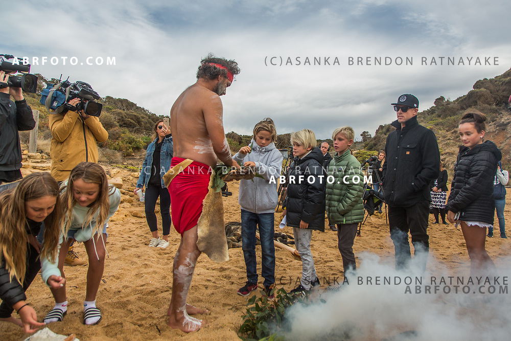 Surfer Mick Fanning lines up with children as they collect gum-leaves used during an Aboriginal smoking ceremony at Bells Beach on the south west coast of Victoria, Australia on the 27th of March 2018. The Aboriginal smoking ceremony is believed to rid one of bad spirits and cleanse the soul. Asanka Brendon Ratnayake for The New York Times.
